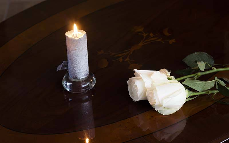 candle and roses on a table in the chapel of rest
