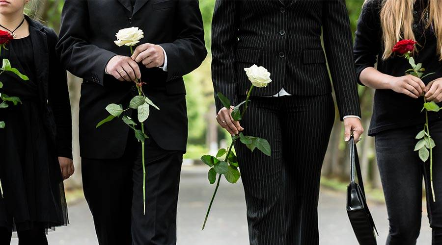 family at funeral service dressed in black and holding single stem roses