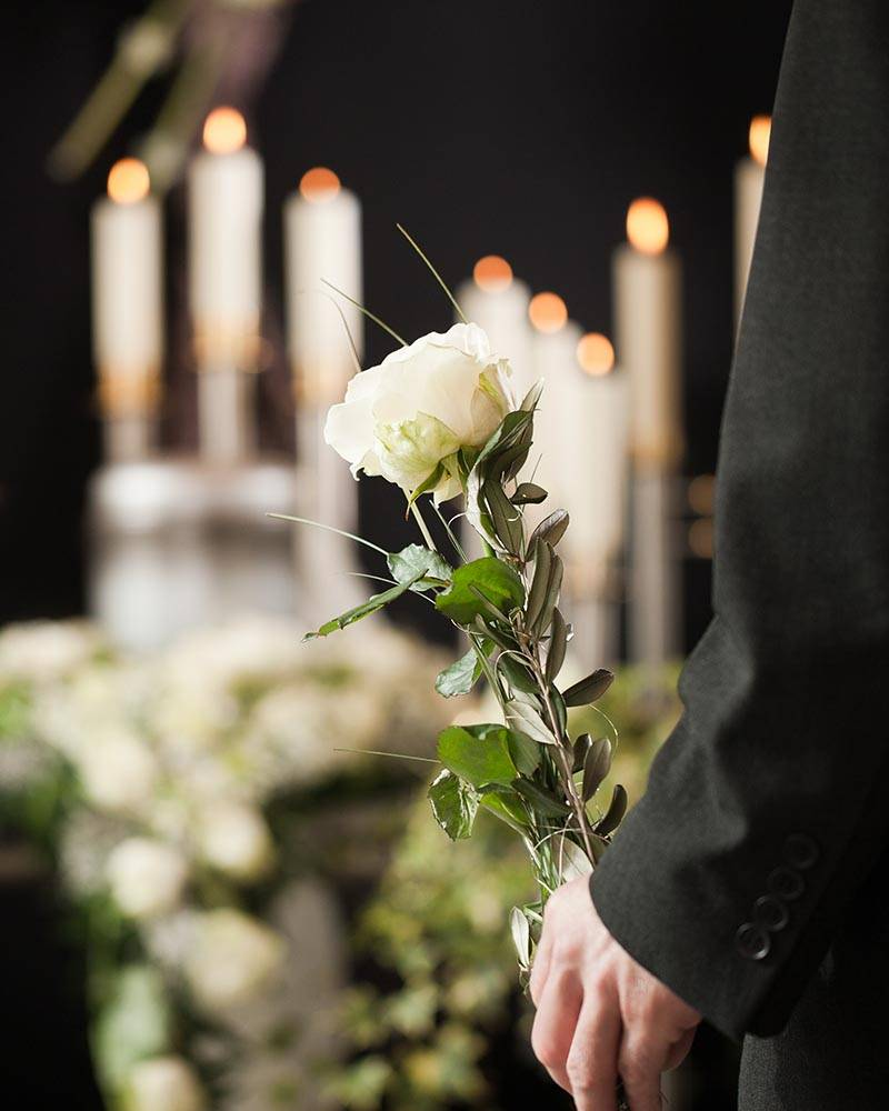 man at a funeral holding a flower