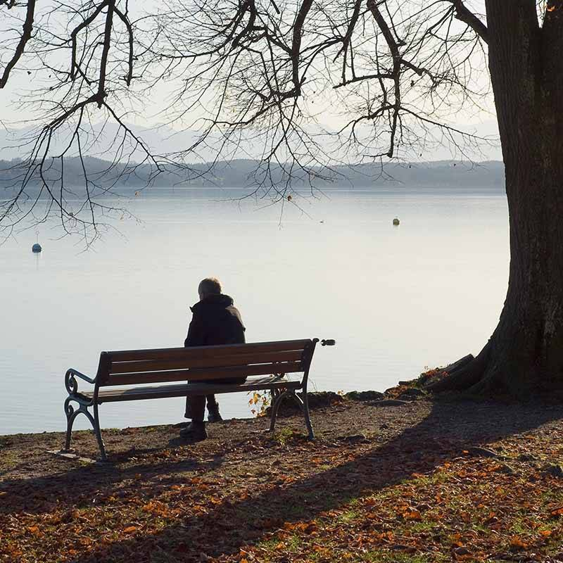 sad person sitting on bench after partner has died